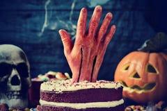 蛋糕冠上了用在一个可怕场面的一只血淋淋的手为万圣夜 免版税库存照片