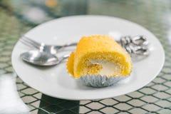 蛋糕卷在白色板材的黄油奶油 免版税库存图片
