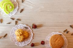 蛋糕卷曲奇饼杯形蛋糕向日葵种子和鹅莓在白色木表上 库存图片