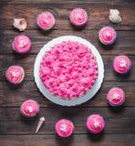 蛋糕和杯形蛋糕与桃红色奶油在土气木背景 桃红色蛋糕 库存图片