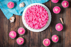 蛋糕和杯形蛋糕与桃红色奶油在土气木背景 桃红色蛋糕 库存照片