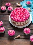 蛋糕和杯形蛋糕与桃红色奶油在土气木背景 库存照片