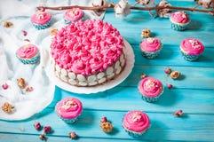 蛋糕和杯形蛋糕与桃红色奶油在蓝色木背景 桃红色蛋糕 图库摄影