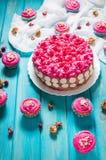 蛋糕和杯形蛋糕与桃红色奶油在蓝色木背景 免版税库存照片