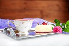 蛋糕和热的茶在一个盘子在木背景 作为背景诱饵概念美元灰色吊异常分支 免版税图库摄影