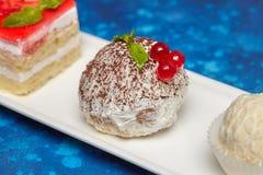 蛋糕和糖果的安排在长的白色板材 图库摄影