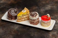 蛋糕和糖果的安排在长的白色板材 免版税库存图片