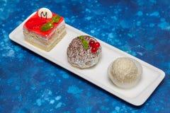 蛋糕和糖果的安排在长的白色板材 库存图片