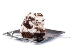 蛋糕在一块板材的有在白色背景的一把匙子的 库存照片