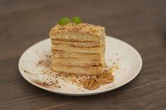 蛋糕在白色板材的拿破仑在木背景 俄国烹调,与奶油的夹心蛋糕,关闭看法 库存图片