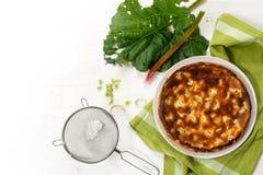 蛋糕或饼在一片绿色洗碗布、大黄茎和叶子,  库存图片