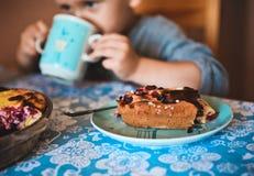 蛋糕板材桌男孩杯子饮用的茶 库存照片