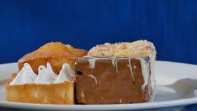 蛋糕用在一块白色板材的樱桃在木板 不同的酥皮点心 蛋糕 免版税库存图片
