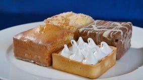 蛋糕用在一块白色板材的樱桃在木板 不同的酥皮点心 蛋糕 图库摄影