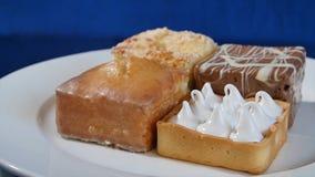 蛋糕用在一块白色板材的樱桃在木板 不同的酥皮点心 蛋糕 免版税库存照片