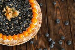 蛋糕用在木桌上的莓果 免版税库存照片