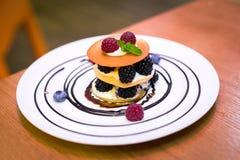 蛋糕用在白色板材的莓果 免版税图库摄影