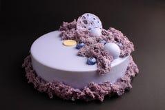 蛋糕用在镜子釉的黑莓奶油甜点装饰用一个分子饼干 免版税库存照片