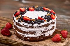 蛋糕裁减与被鞭打的奶油和草莓的在木桌上结果实 库存图片