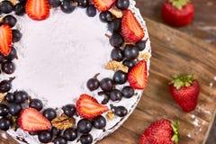 蛋糕裁减与被鞭打的奶油和草莓的在木桌上结果实 免版税库存照片