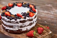 蛋糕裁减与被鞭打的奶油和草莓的在木桌上结果实 免版税库存图片