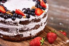 蛋糕裁减与被鞭打的奶油和草莓的在木桌上结果实 库存照片