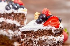 蛋糕裁减与被鞭打的奶油和草莓的在木桌上结果实 图库摄影
