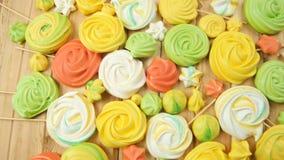 蛋糕装饰的许多不同的五颜六色的甜蛋白牛奶酥在背景的木桌上说谎在慢动作关闭 股票视频