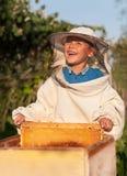 蜂农在蜂房工作的一个年轻男孩 养蜂业 免版税图库摄影