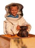 蜂农在蜂房工作的一个年轻男孩 免版税库存图片