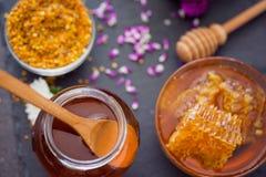 蜂窝和蜂蜜在玻璃瓶子在黑台式视图 免版税库存图片