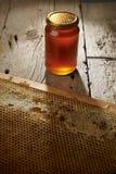 蜂窝用在一个花瓶的新鲜的蜂蜜在木桌上。 免版税库存图片
