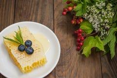 蜂窝用蓝莓和薄菏 木背景 顶视图 库存图片