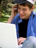 蜂窝电话膝上型计算机少年 免版税库存照片
