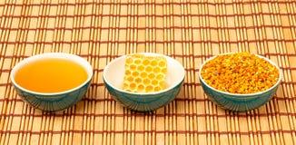 蜂蜜、蜂窝和花粉在碗 免版税图库摄影