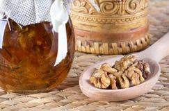 蜂蜜和坚果在土气桌上 库存照片