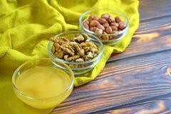 蜂蜜和坚果在玻璃花瓶 免版税图库摄影