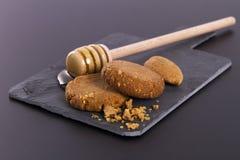 蜂蜜和曲奇饼在纸板页岩在黑背景 免版税库存图片