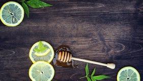 蜂蜜和柠檬 蜂蜜棍子和切片在向求爱的切的柠檬 免版税库存图片