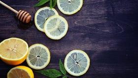 蜂蜜和柠檬 蜂蜜棍子和切片在向求爱的切的柠檬 免版税图库摄影