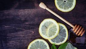 蜂蜜和柠檬 蜂蜜棍子和切片在向求爱的切的柠檬 库存图片