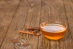 蜂蜜和桂香在一张木桌上 免版税库存照片