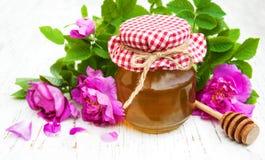 蜂蜜和玫瑰色花 库存照片