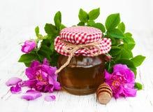 蜂蜜和玫瑰色花 免版税库存图片
