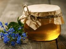 蜂蜜和花在老桌上 免版税库存图片