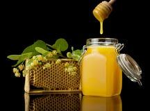 蜂蜜和蜂窝的木绞拌器,隔绝在黑色 免版税库存图片