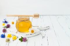 蜂蜜和野花在土气老木背景 免版税库存照片
