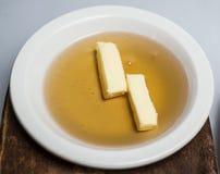蜂蜜和黄油在白色板材 库存图片