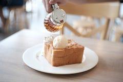 蜂蜜多士用香草冰淇凌和打好的奶油在白色板材 免版税图库摄影