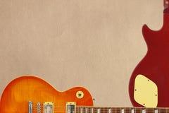 蜂蜜桃花心木吉他身体镶有钻石的旭日形首饰的电吉他和后面在概略的纸板背景的,与大量拷贝空间 库存图片